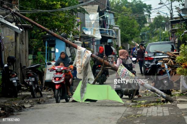 Indonesian motorists drive through a damaged area after a tornado hit Sidoarjo on November 23 2017 More than 700 homes damaged and about 35 people...