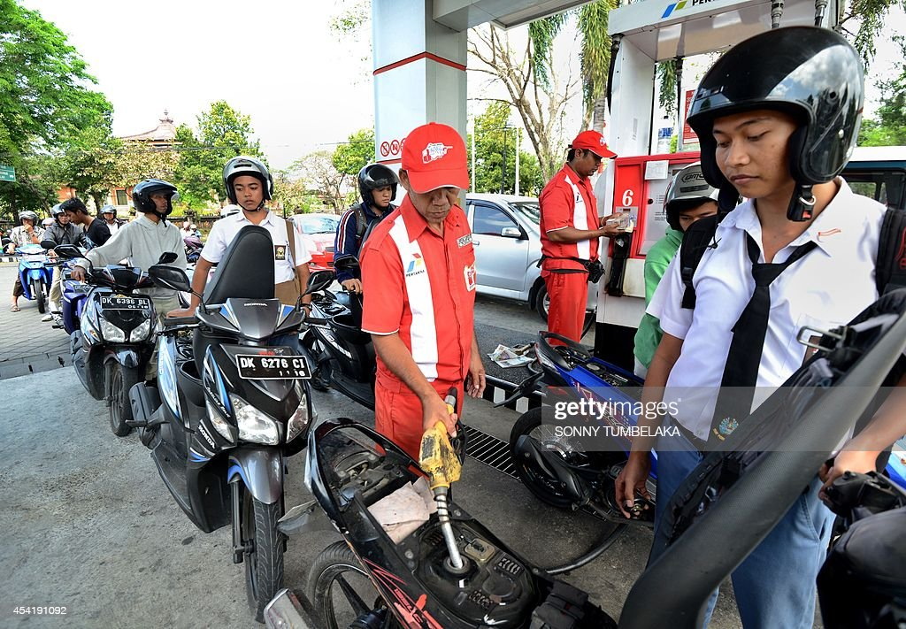 Indonesian motorists queue up at the pumps at a petrol station in Denpasar on the Indonesian tourist island of Bali on August 26, 2014 as major cities across the country are hit with a shortage of subsidized fuel forcing long lines and the closure of service stations. Economists say Indonesia must phase out the huge fuel subsidies that make petrol prices in Indonesian among the cheapest in Asia but gobble up about 20 percent of the state budget. The subsidies are historically a tense political issue in Indonesia, where fuel price hikes to reduce the payouts have been met with massive protests and caused divisions between coalition partners in government.