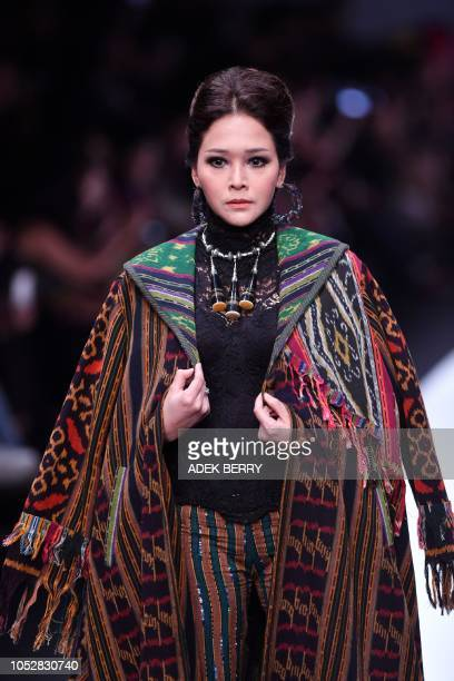 Indonesian musician Maia Estianty presents creations by Indonesian designer Anne Avantie during the 2019 Jakarta Fashion Week to seek donations for...