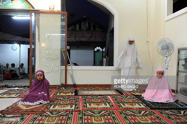 Indonesian Muslim girls pray after an Iftar meal or the breaking of the fast consisting of fruits rice cakes donuts tea and water that comes with...
