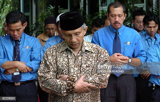 Indonesian Muslim leader Amien Rais and Indonesian TV journalists and staff of Metro TV station pray together in Jakarta 22 February 2005 for the...