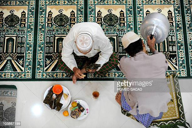 Indonesian Muslim men partake in an Iftar meal or the breaking of the fast consisting of fruits rice cakes donuts tea and water that comes with gifts...