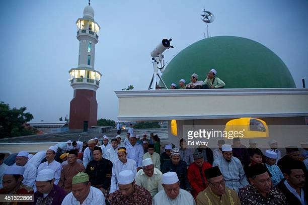 Indonesian Muslim men pray as a man looks through a telescope to sight the new moon the sign of the start of the Islamic holy month Ramadan on June...