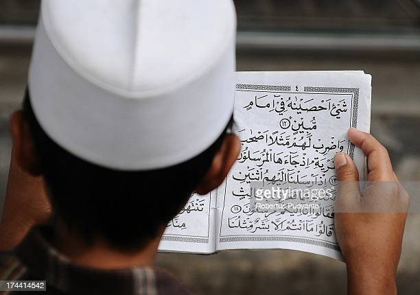 Indonesian Muslim men reads Quran to celebrate the holy day of Nuzulul Quran in Ampel Mosque on July 25 2013 in Surabaya Indonesia Nuzulul Quran is...