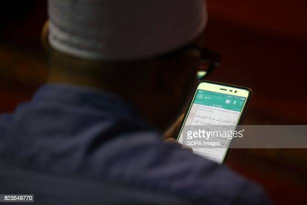 Indonesian muslim reads the Koran in his mobile phone during the holy month of Ramadan in istiqlal Mosque