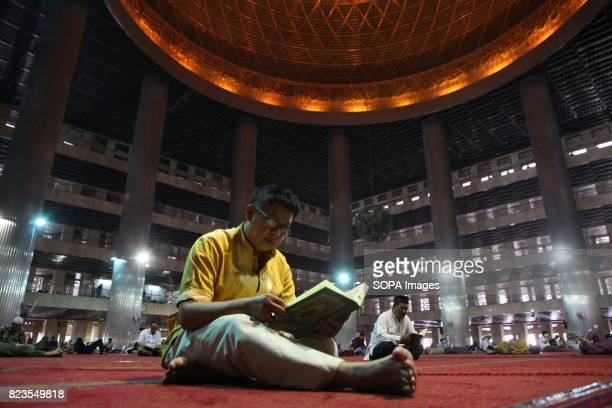 Indonesian Muslim reads the Koran near the other take a nap during the holy month of Ramadan in istiqlal Mosque