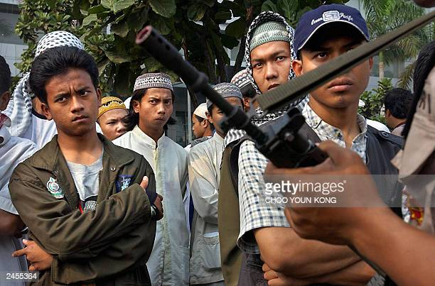 Indonesian Muslim supporters from a school of Abu Bakar Bashir's look on outside the courthouse where the verdict in the Muslin cleric's trial is...
