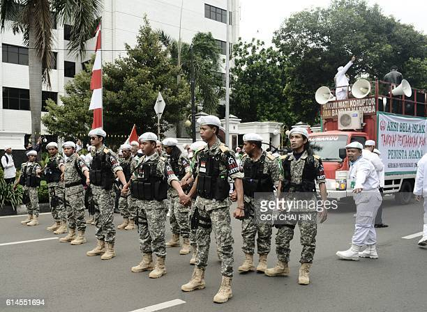 Indonesian Muslim volunteers gather to protect their leaders who are leading a protest against Jakarta governor Basuki Tjahaja Purnama known by his...