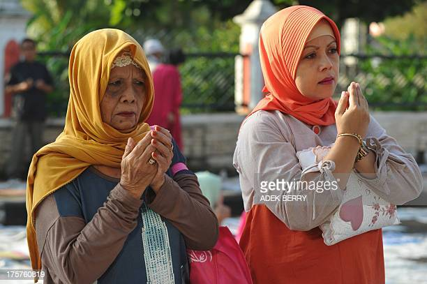 Indonesian Muslim women pray as a cleric concludes Eid alFitr prayers in Cianjur West Java on August 8 2013 Tens of millions of Muslims in Indonesia...