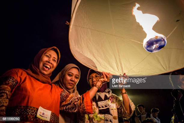 Indonesian muslim women prepare release a lantern into the air on Borobudur temple during celebrations for Vesak Day on May 10 2017 in Magelang...