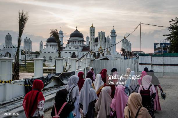 Indonesian muslim women walk as Baiturrahman grand mosque is seen on March 22 2017 in Banda Aceh Indonesia Indonesia's Aceh Province on the northern...