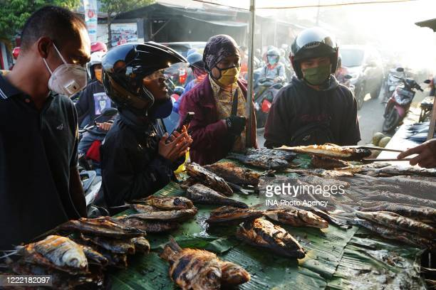 Indonesian Muslims buy smoked grilled fish in a local market in Makassar during the fasting month of Ramadan amid coronavirus threats.