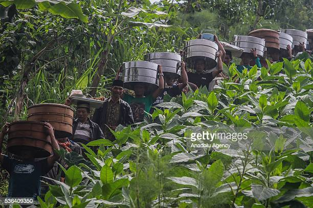 Indonesian muslims carry boxes of food during the Javanese ritual called Nyadran at Purwoloyo Cemetery in Boyolali Central Java Indonesia on June 01...
