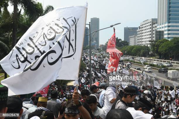 Indonesian Muslims carry flags and banners march toward Parliament to mark the 52nd anniversary of the murder of six army generals and a young...