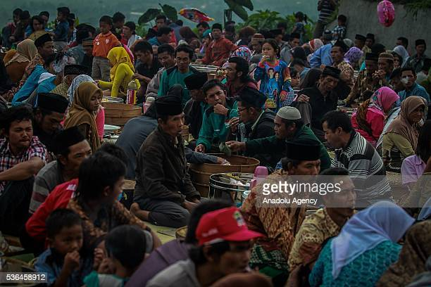 Indonesian muslims eat their food all together after pray for the souls of their ancestor during the Javanese ritual called Nyadran at Purwoloyo...