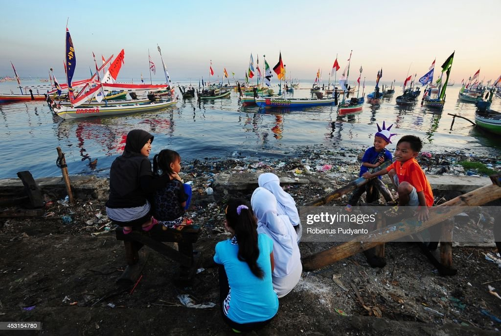Indonesian Muslims fisherman and the family prepare to attend the Petik Laut ceremony on August 4, 2014 in Pasuruan, Java, Indonesia. Indonesian Muslims working as fishermen have a tradition called Petik Laut, a ceremony in which they make offerings to Gods of the sea and give thanks for a plentiful harvest as part of Eid celebrations. They decorated the boat, make offerings, and sail to the sea follow the Petik Laut ceremony.