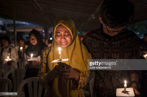 Indonesian Muslims gather during a candlelight vigil to remember the victims of deadly suicide bombings carried out one year ago, outside the Saint...