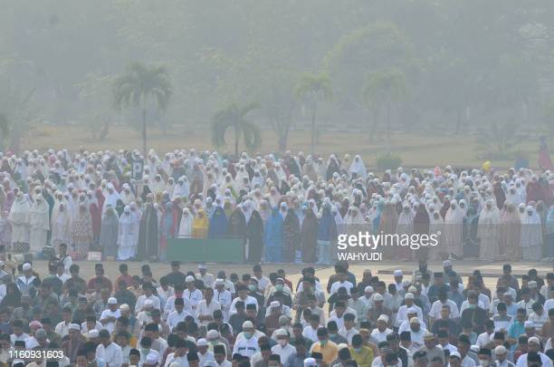 Indonesian Muslims gather for Idul Adha prayers at the An Nur mosque in Pekanbaru Riau as thick haze from the forest fires blanket the area on August...