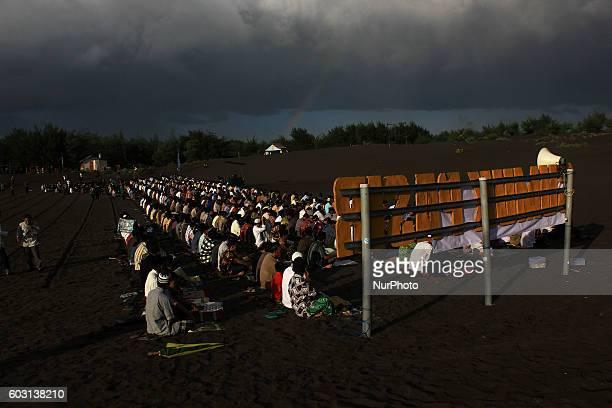 Indonesian muslims gather to perform Eid AlAdha prayer at Sand dunes Parangkusumo Beach on September 12 2016 in Yogyakarta Indonesia Muslims...