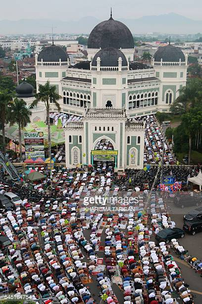 Indonesian Muslims gather to pray outside the overpacked AlMahsun mosque in Medan to mark the Eid alFitr in Medan Indonesian Muslims celebrate Eid...
