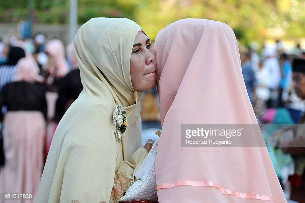 Indonesian Muslims greet each other during Eid AlFitr celebration on July 17 2015 in Surabaya Indonesia Muslims worldwide observe the Eid AlFitr...