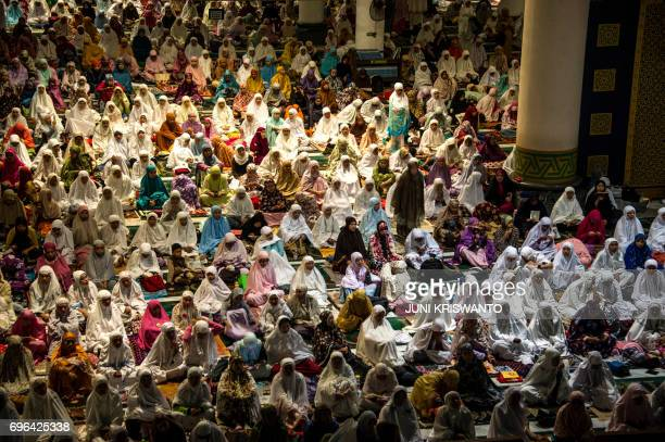 TOPSHOT Indonesian Muslims offer prayers and read the koran on the 21st day of holy month of Ramadan at a Al Akbar mosque in Surabaya early on June...