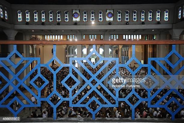 Indonesian Muslims perform Eid AlAdha prayer at AlAkbar Mosque on October 5 2014 in Surabaya Indonesia Muslims worldwide celebrate Eid AlAdha to...