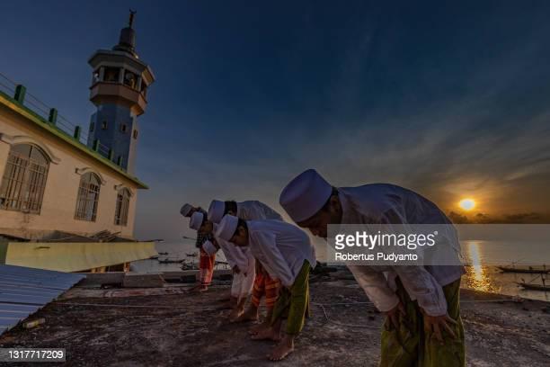 Indonesian Muslims perform Eid Al-Fitr prayer at Al-Mabrur mosque on May 13, 2021 in Surabaya, Indonesia. Muslims worldwide observe the Eid Al-Fitr...