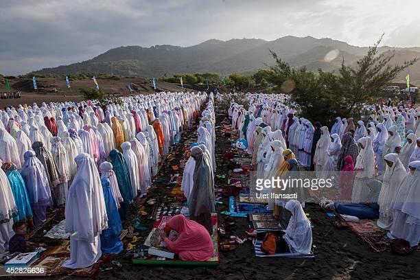 Indonesian muslims perform Eid AlFitr prayer on 'sea of sands' at Parangkusumo beach on July 28 2014 in Yogyakarta Indonesia Eid AlFitr marks the end...