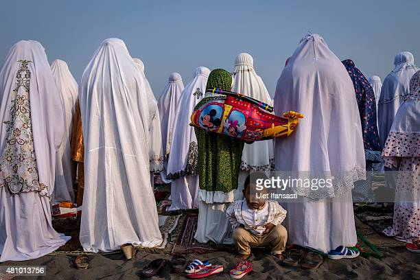 Indonesian muslims perform Eid AlFitr prayer on 'sea of sands' at Parangkusumo beach on July 17 2015 in Yogyakarta Indonesia Eid AlFitr marks the end...
