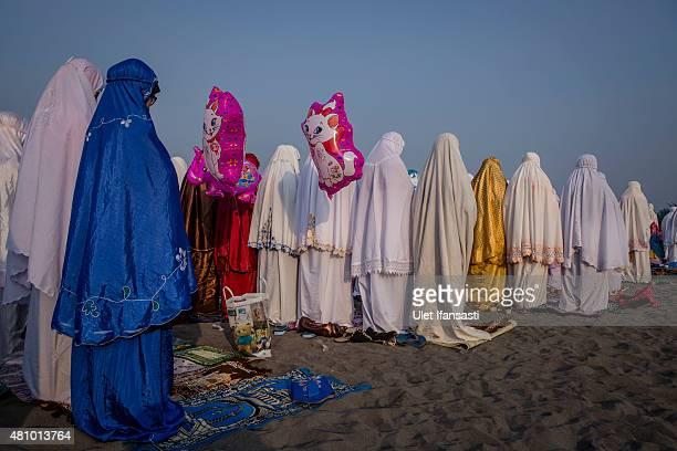 Indonesian muslims perform Eid AlFitr prayer on 'sea of sands' at Parangkusumo beach on July 17 2015 in Yogyakarta Indonesia Eid AlFitr marks the end...