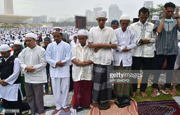 Indonesian Muslims pray in the rain at Jakarta's National Monument Park during a rally against Jakarta's Christian Governor Basuki Tjahaja Purnama...