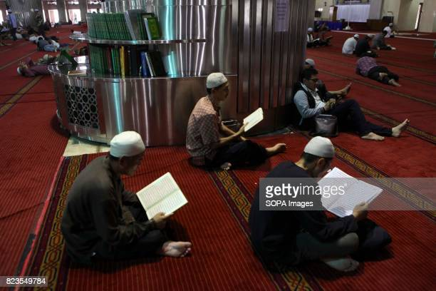 Indonesian Muslims read the Koran near the other take a nap during the holy month of Ramadan in istiqlal Mosque
