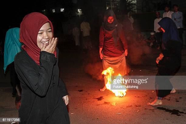 Indonesian Muslims seen playing a soccer game using a fireball made from a coconut from a palm tree soaked in kerosene as they take part in the...