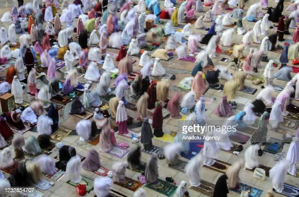 Indonesian Muslims wear protective face masks and maintain social distancing attend the Eid al-Fitr prayer amid the coronavirus pandemic at Kubah...