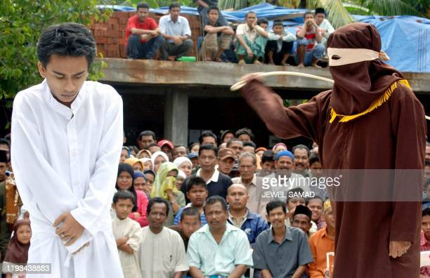 Indonesian Nasrul Mubin is caned in public by an ''algojo'' or veiled lawenforcement official after he was found guilty of gambling before a Sharia...