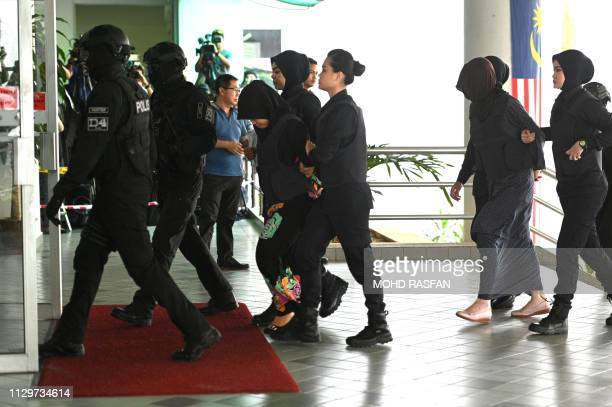 Indonesian national Siti Aisyah and Vietnamese national Doan Thi Huong are escorted by Malaysian police at the Shah Alam High Court outside Kuala...