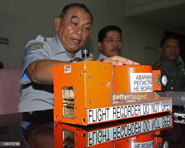 Indonesian National Transportation Safety Board chief Tatang Kurniadi speaks next to the flight data recorder of a crashed Russian passenger jet...