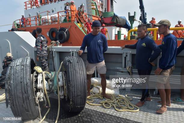 TOPSHOT Indonesian navy divers look at the wheels of the illfated Lion Air flight JT 610 which were recovered from the sea north of Karawang on...