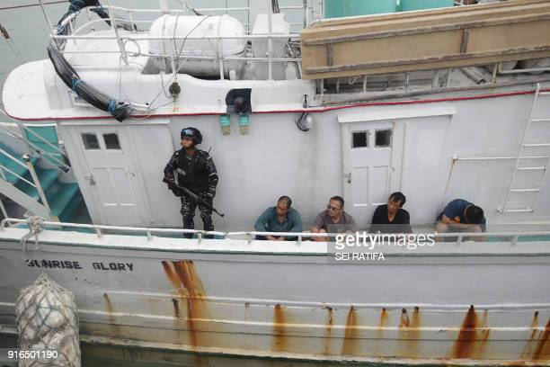 Indonesian navy officer guards the crews of Singapore flag MV Sunrise Glory in Batam island on February 10 2018 as they were arrested in Phillip...