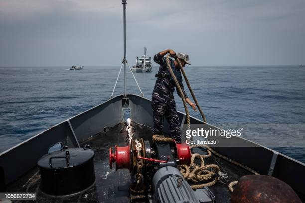 Indonesian navy personnel searching for victims and fuselage of the Lion Air flight JT 610 at the sea on November 3 2018 in Jakarta Indonesia...