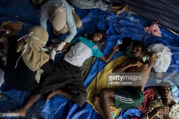 Indonesian nurses tend to Bangladeshi migrants in the new confinement area in the fishing town of Kuala Langsa in Aceh province on May 16 2015 where...
