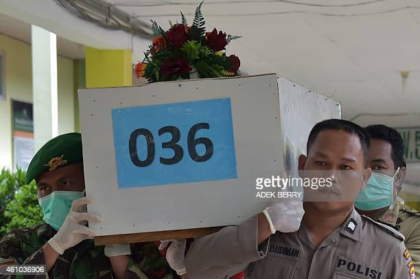 Indonesian officers carry a coffin with the remains of a passenger of the AirAsia flight 8501 at Sultan Imanuddin hospital in Pangkalan Bun on...