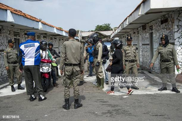 Indonesian officers from the city administration police detain unmarried couples after a raid at a hotel in Surabaya on February 14 2018 Valentine's...