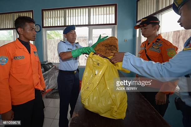 Indonesian officers hold newly recovered wreckage from AirAsia flight QZ8501 found during search operations in the Java sea in Pangkalan Bun on...