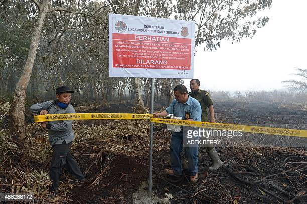 Indonesian officials from Ministry of Environment and Forestry seal a burnt area for investigation in Rimbo Panjang Riau province on September 15...