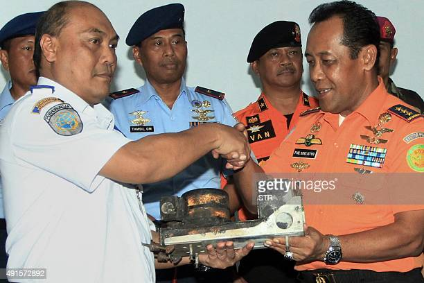Indonesian officials from the National Search and Rescue Agency chief Air Marshal FH Bambang Soelistyo turns over the recovered blackbox of the...