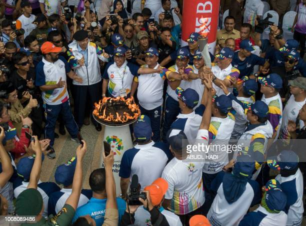 Indonesian officials surround the flame during the torch relay of the 2018 Asian Games in Banda Aceh on July 31 2018 Jakarta and Palembang will host...