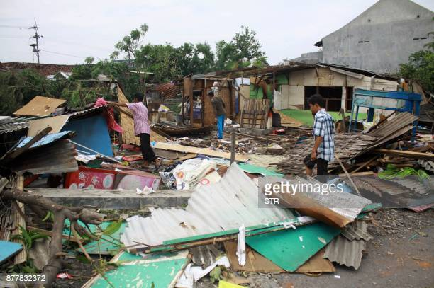 Indonesian people check damages after a tornado hit Surabaya on November 23 2017 More than 700 homes damaged and about 35 people injured after...