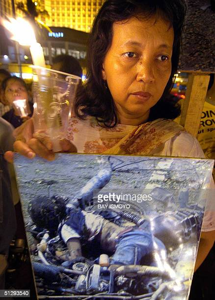 Indonesian people hold candles and pictures of Australian embassy bomb attacks victims as they committed to reject any terrorism act in Jakarta 12...